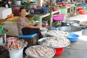 smiling Vietnamese lady selling fresh seafood including squid on the market in Vietnam