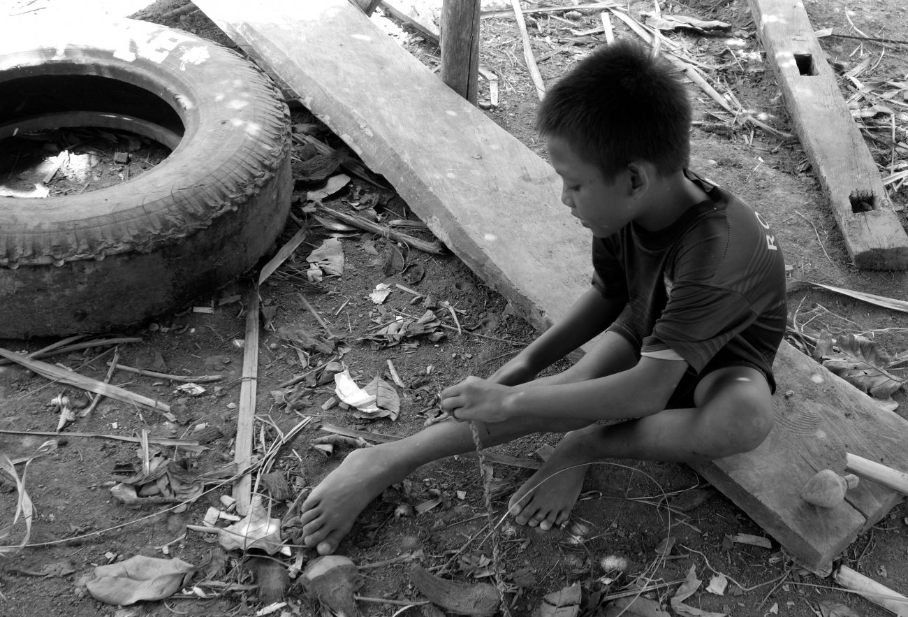 Indonesian boy makes a string for a wooden toy, Lombok, Indonesia